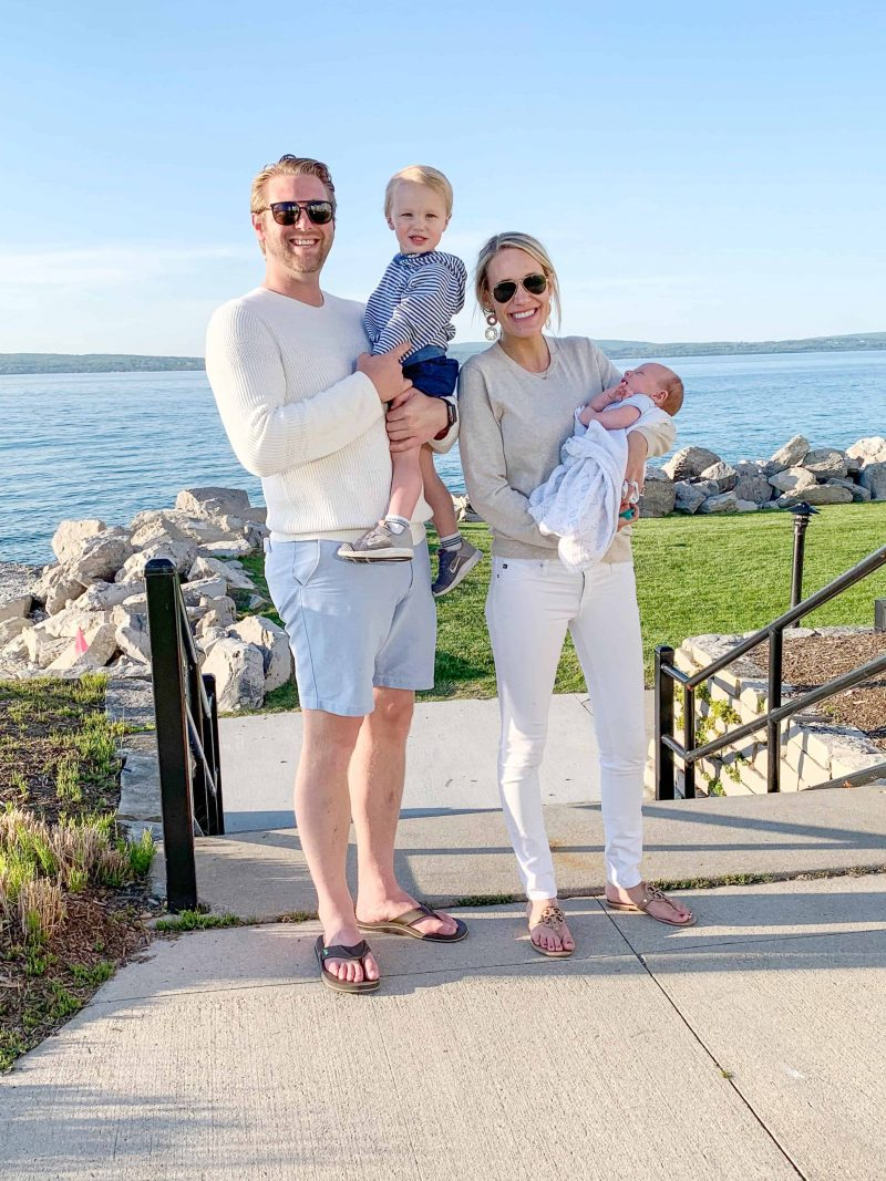 family with two boys in petoskey michigan | Family Vacation Destinations by popular Michigan travel blog, The House of Navy: image of a husband and wife standing together outside in front of a lake while holding their two young boys.