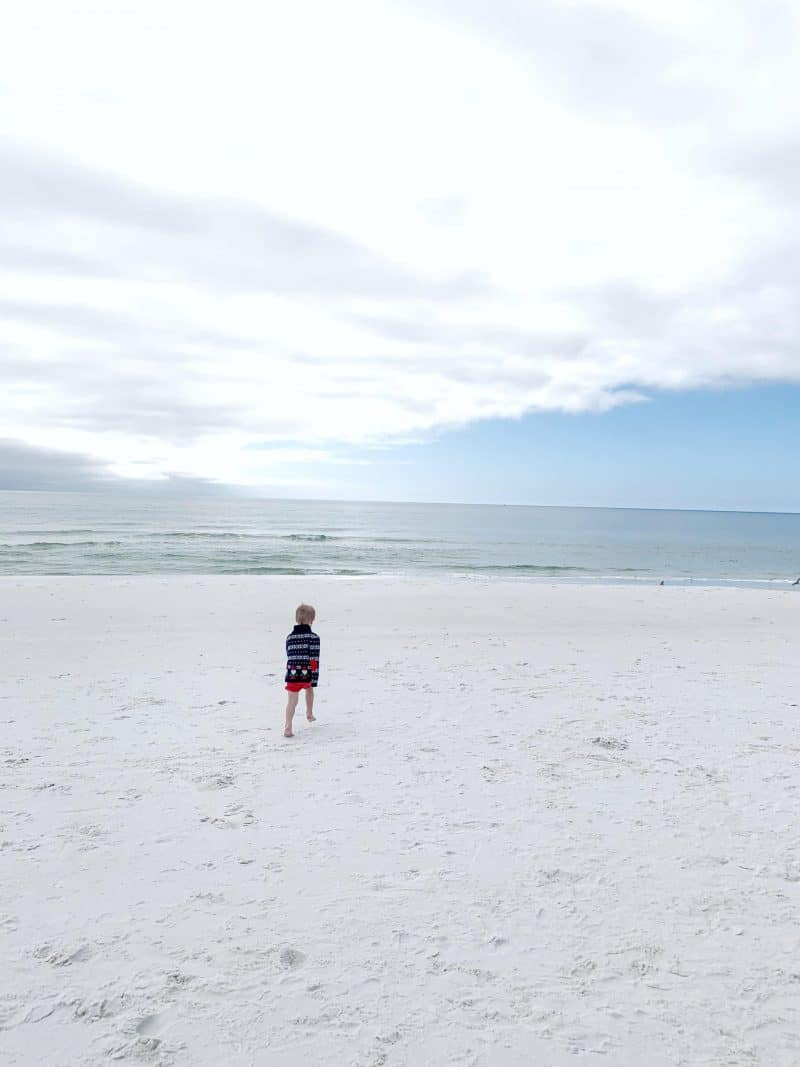The Ultimate 30A Travel Guide for Families featured by top US travel blog, House of Navy: image of boy running on beach in Florida
