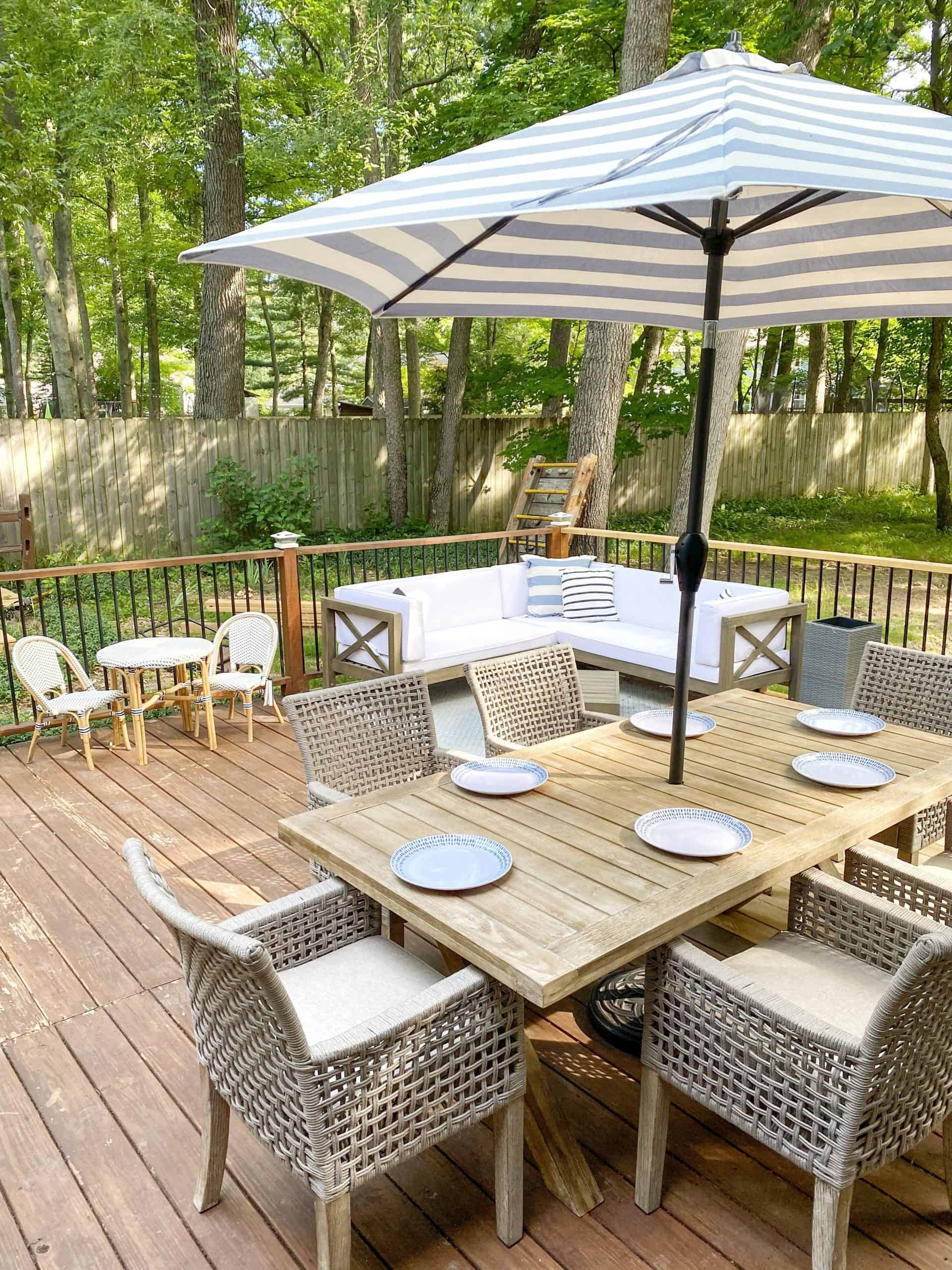 preppy outdoor patio decor |covered preppy patio decor | Preppy Outdoor Decor by popular Michigan life and style blog, The House of Navy: image of a patio decorated with a outdoor dining set, light blue and white stripe umbrella, sectional couch with white cushions and a kids bistro table and chair set.