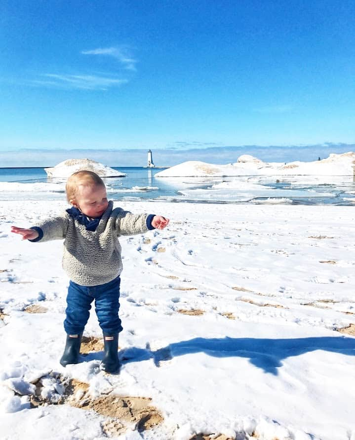 baby boy on beach in snow | Living in Michigan by popular Michigan lifestyle blog, The House of Navy: image of a little boy standing in some snow near a lake in Frankfort, MI.