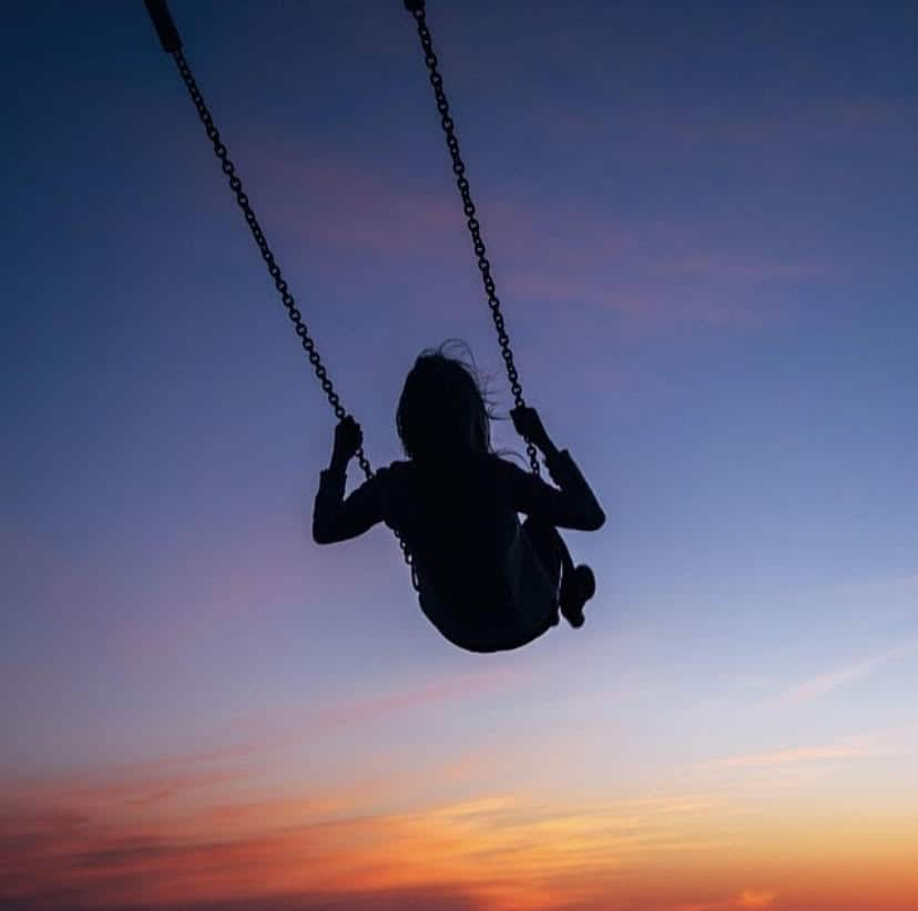 woman swinging into sunset | Living in Michigan by popular Michigan lifestyle blog, The House of Navy: image of a woman swinging on a swing at sunset in Holland, MI.