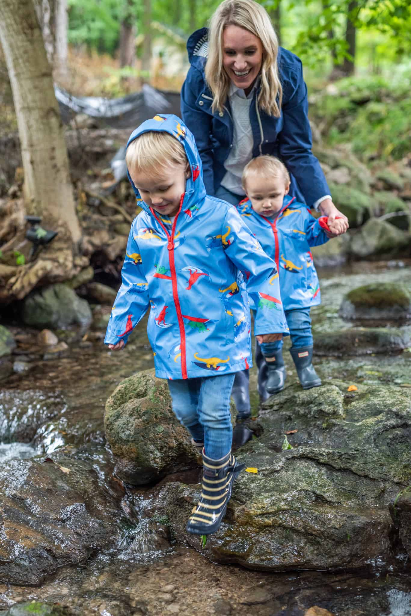 Bath and Bedtime Routine with Aveeno® Baby featured by top Michigan lifestyle blogger, The House of Navy: mom and boys playing in stream | Aveeno Baby by popular Michigan motherhood blog, House of Navy: image of a mom and her two young boys playing outside in a stream.