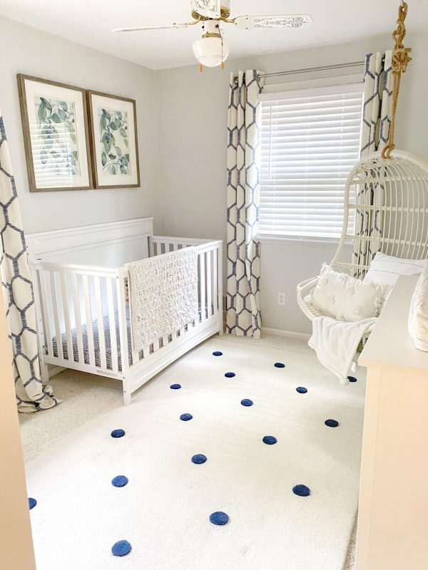 baby crib in nursery  | Nautical Nursery Decor by popular Michigan life and style blog, The House of Navy: image of a nursery decorated with a white crib, white dresser, blue and white honeycomb print drapes, white ceiling fan, botanical prints, white rug with blue dots, and a hanging rattan chair.