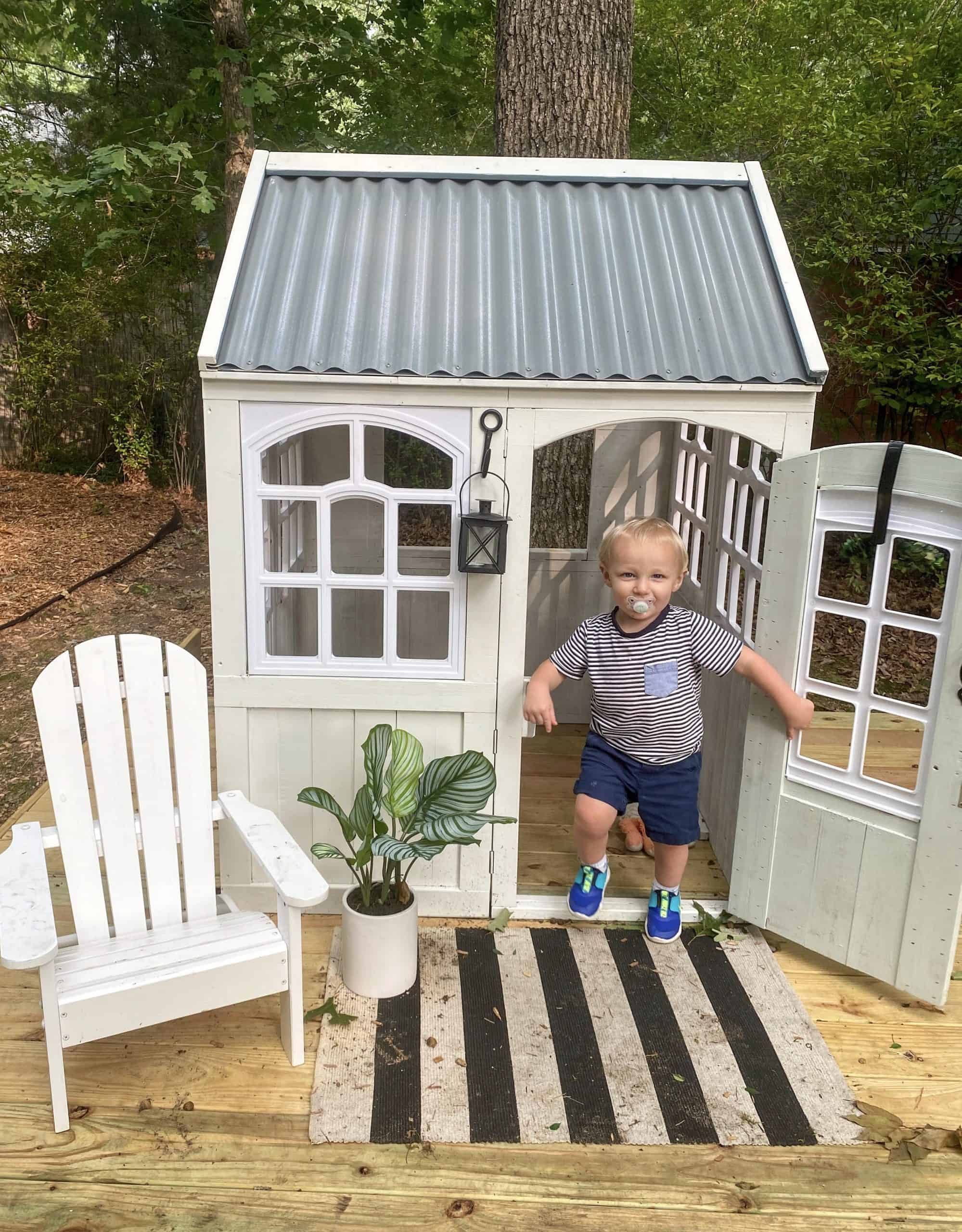 Bath and Bedtime Routine with Aveeno® Baby featured by top Michigan lifestyle blogger, The House of Navy: little boy and playhouse makeover | Aveeno Baby by popular Michigan motherhood blog, House of Navy: image of a  young boy playing in an outdoor playhouse.