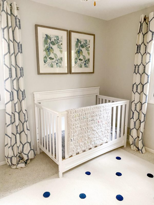 baby crib in nursery |Nautical Nursery Decor by popular Michigan life and style blog, The House of Navy: image of a nursery decorated with a white crib, white dresser, blue and white honeycomb print drapes, white ceiling fan, botanical prints, and white rug with blue dots.