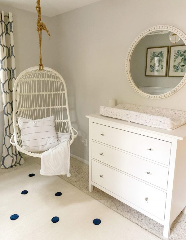serena & lily hanging rattan chair |Nautical Nursery Decor by popular Michigan life and style blog, The House of Navy: image of a nursery decorated with a white crib, white dresser, blue and white honeycomb print drapes, white ceiling fan, botanical prints, round white mirror, white rug with blue dots, and a hanging rattan chair.