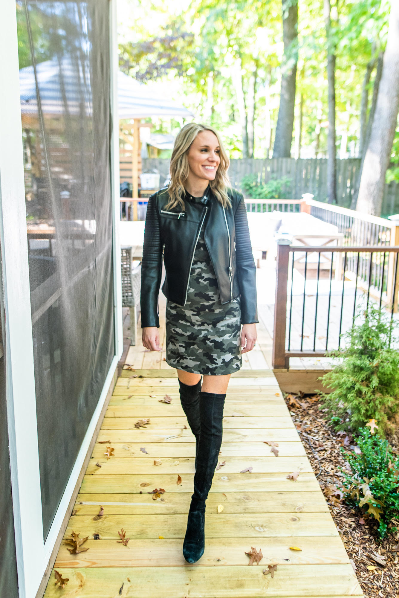 fashionable preppy mom in camo dress |Fall Clothing by popular Michigan fashion blog, The House of Navy: image of a woman wearing the Duffield Lane Amber Dress with a leather jacket and black suede over the knee boots.