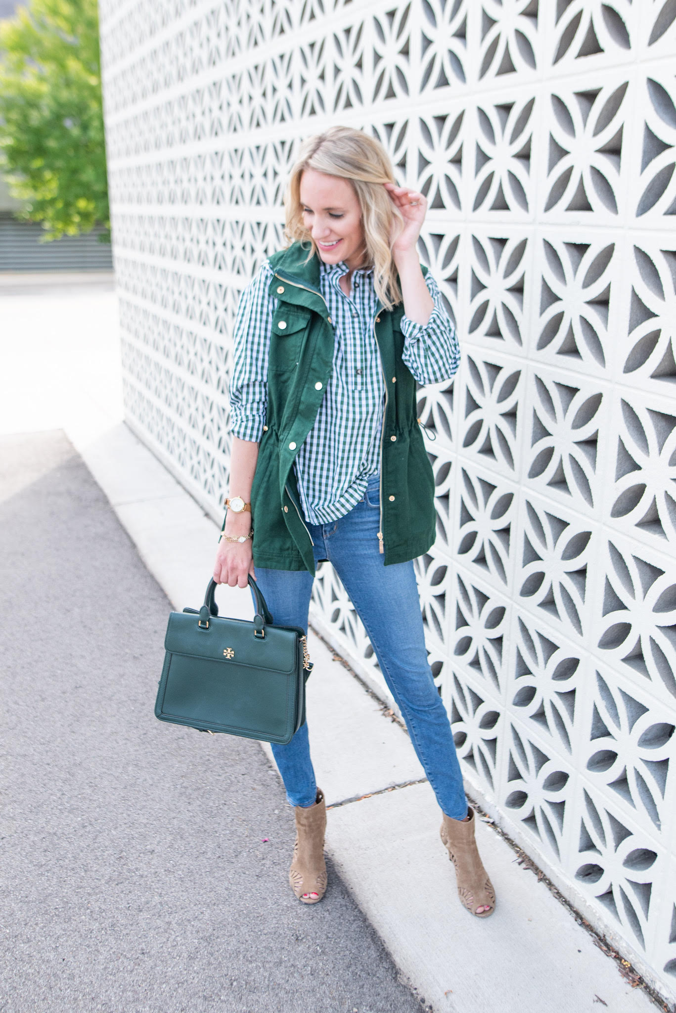 fashionable preppy mom in hunter green outfit |Fall Clothing by popular Michigan fashion blog, The House of Navy: image of a woman wearing the Duffield Lane Sumner Vest with a pair of light wash jeans, peep toe ankle boots, and plaid button down shirt.