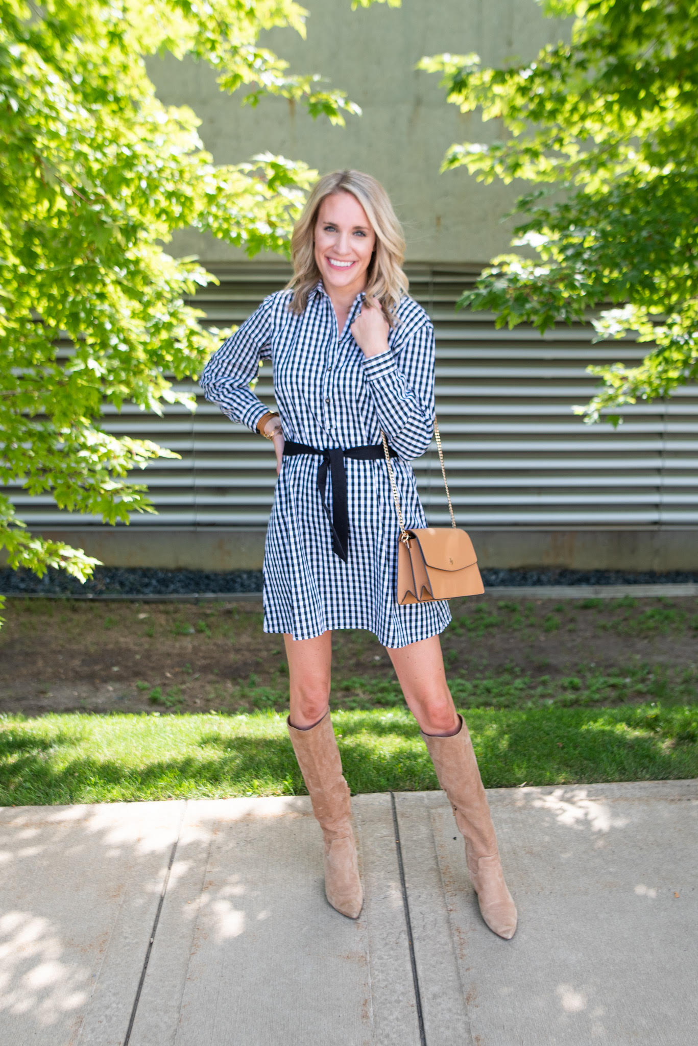fashionable preppy mom in gingham dress |Fall Clothing by popular Michigan fashion blog, The House of Navy: image of a woman wearing the Duffield Lane Keys Dress with a pair of tan suede knee high boots.