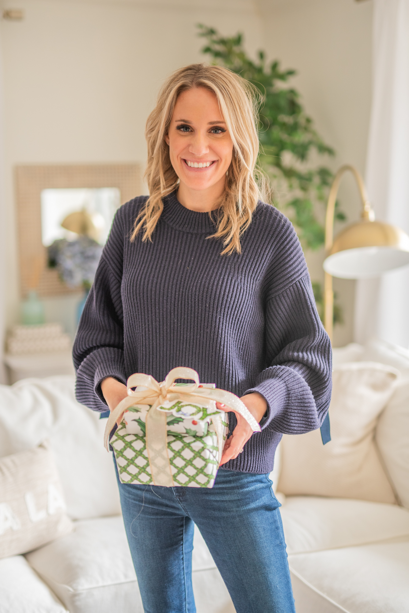 woman holding wrapped christmas gifts | Gifts Under $50 by popular Michigan lifestyle blog, The House of Navy: image of a woman wearing a blue sweater and pair of jeans and holding a wrapped present.