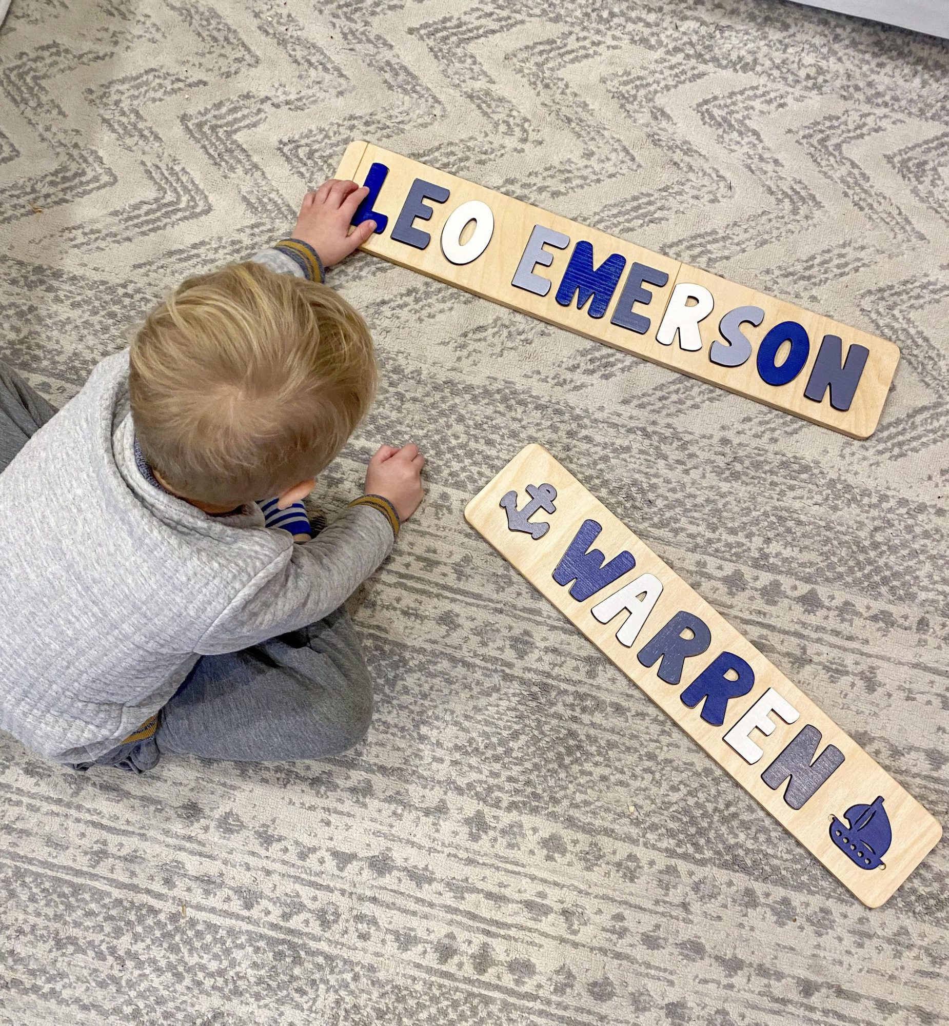 little boy playing with personalized name puzzle | Gifts for Toddlers by popular Michigan motherhood blog, The House of Navy: image of a little boy doing a name puzzle.