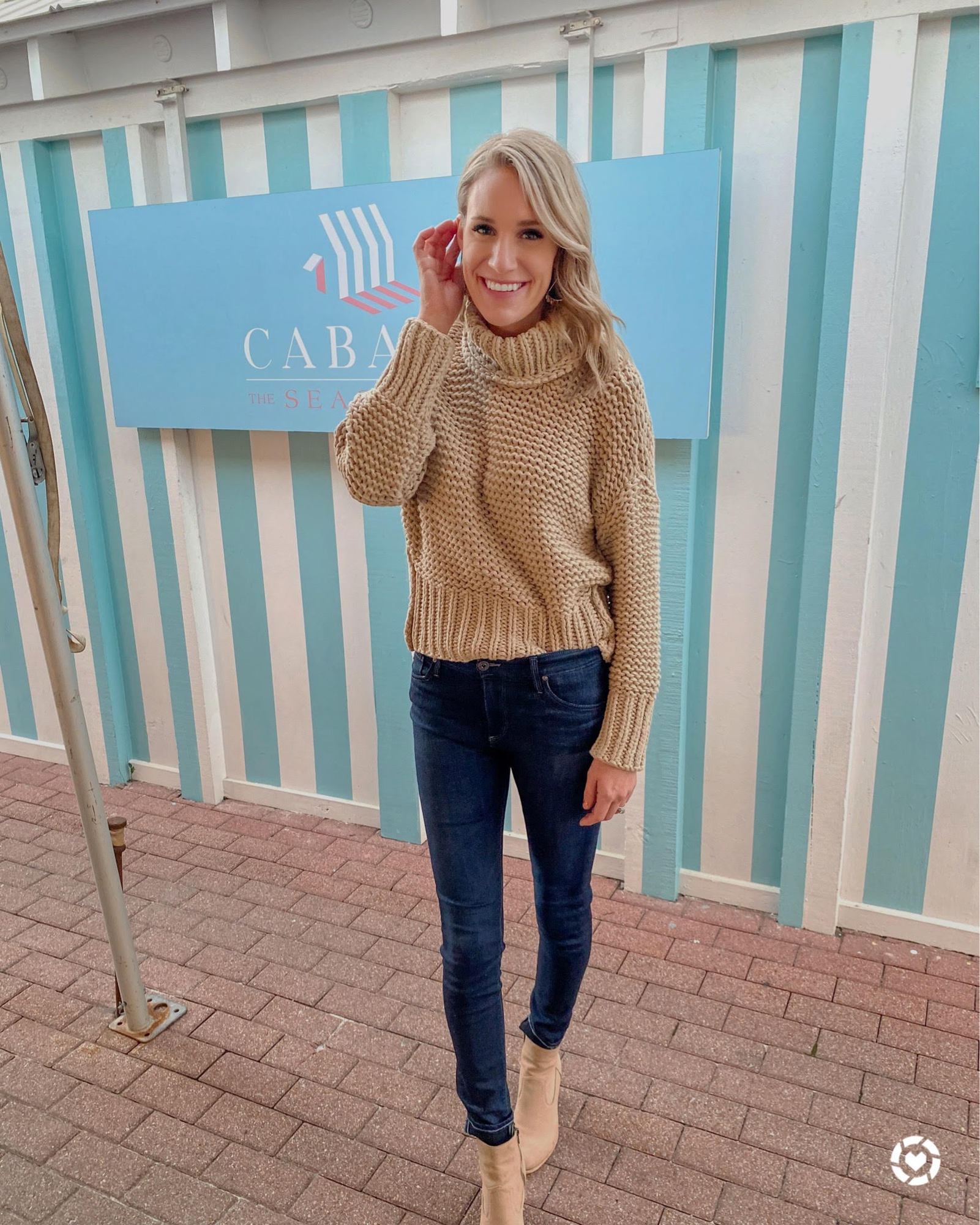 women in winter sweater | Winter Sweaters by popular Michigan fashion blog, The House of Navy: image of a woman wearing a tan cable knit sweater, dark denim jeans, and tan suede ankle boots.