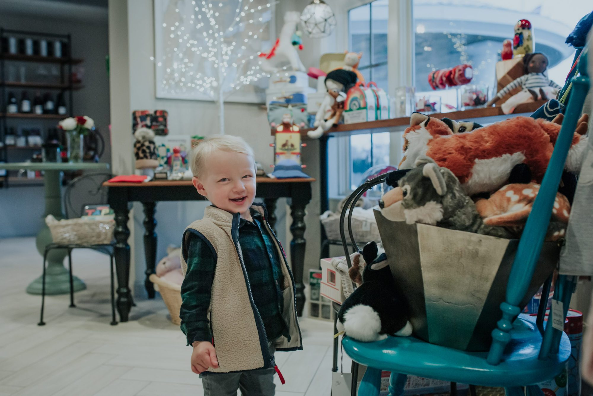 toddler boy smiling in toy shop |Inn at Bay Harbor by popular Michigan travel blog, The House of Navy: image a  little boy looking at a display of stuffed animals.