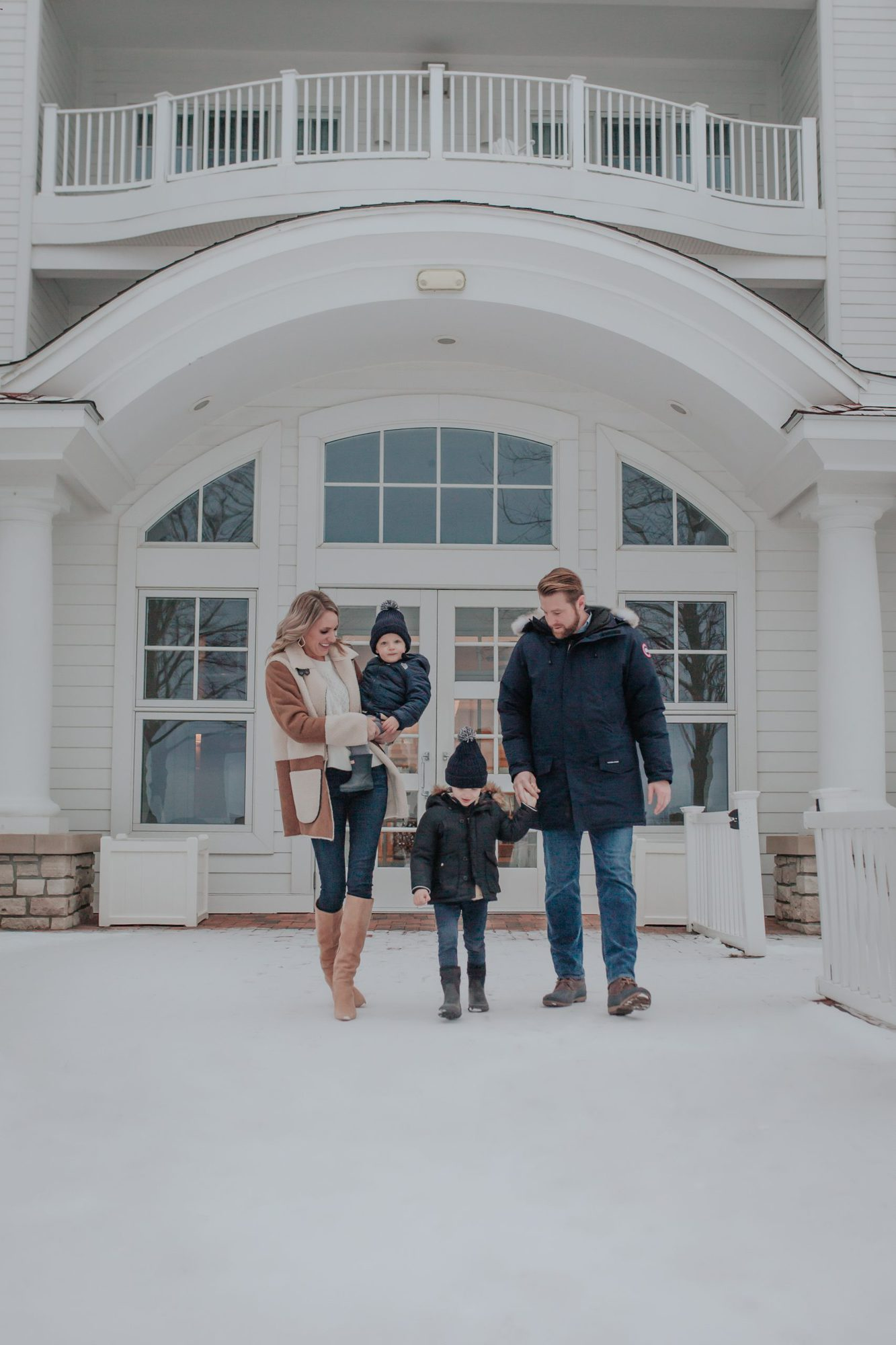 family walking outside in winter at Bay Harbor |Inn at Bay Harbor by popular Michigan travel blog, The House of Navy: image of a family walking outside at the Inn at Bay Harbor.