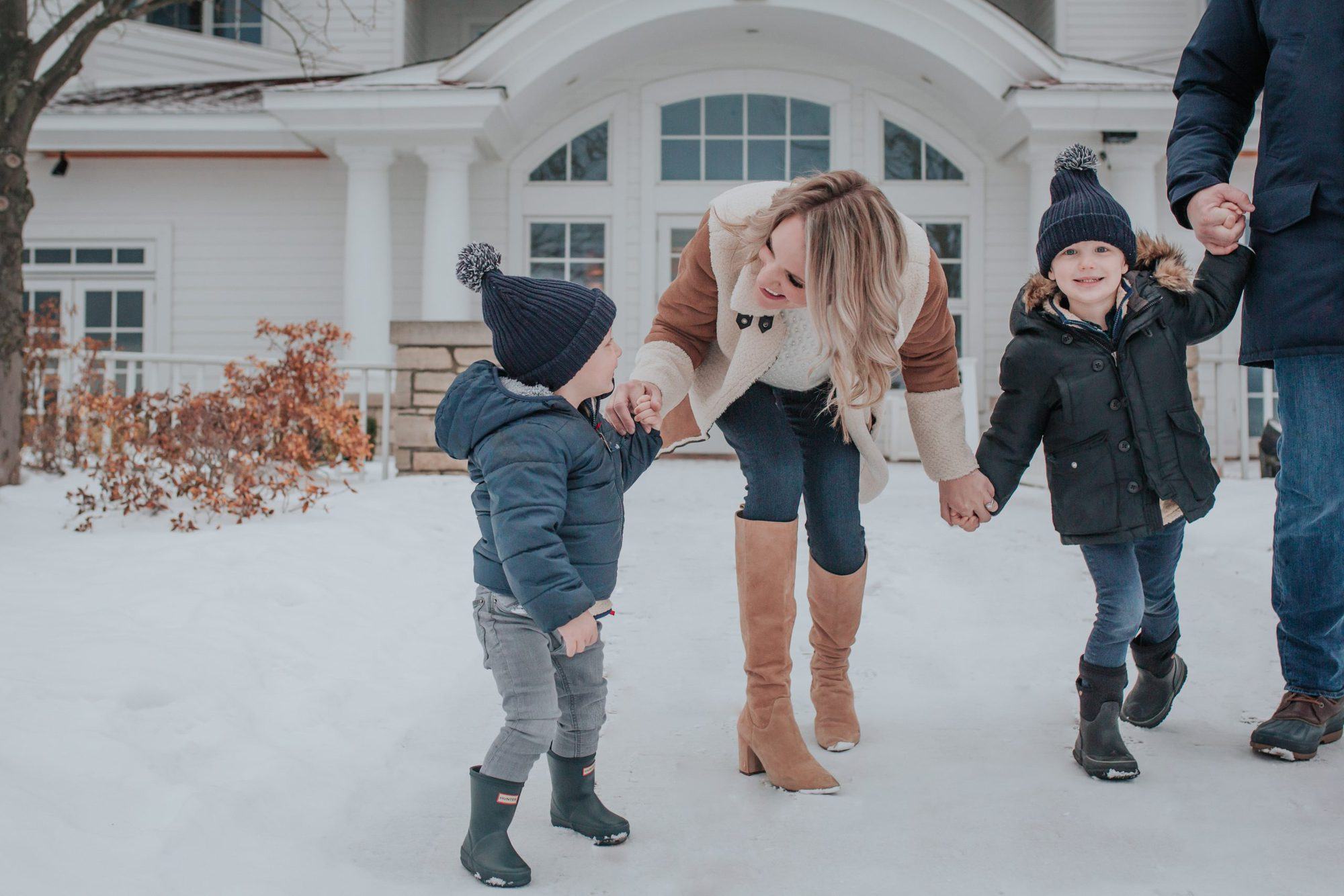 mother and sons walking outside in winter |Inn at Bay Harbor by popular Michigan travel blog, The House of Navy: image of a family standing outside at the Inn at Bay Harbor.