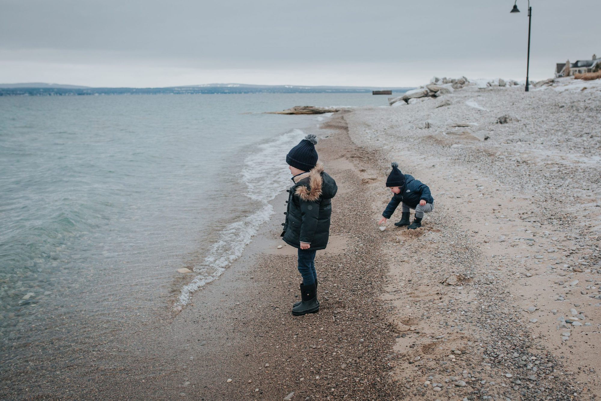 little boys skipping stones on Lake Michigan in winter |Inn at Bay Harbor by popular Michigan travel blog, The House of Navy: image of two little boys standing on a rocky beach next to some water.