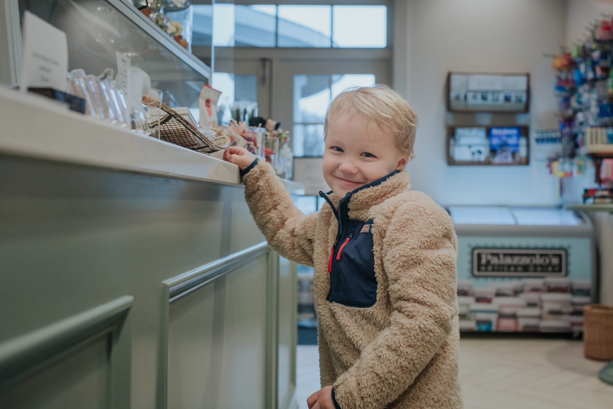little boy smiling in cafe shop |Inn at Bay Harbor by popular Michigan travel blog, The House of Navy: image of a little boy in a cafe shop.