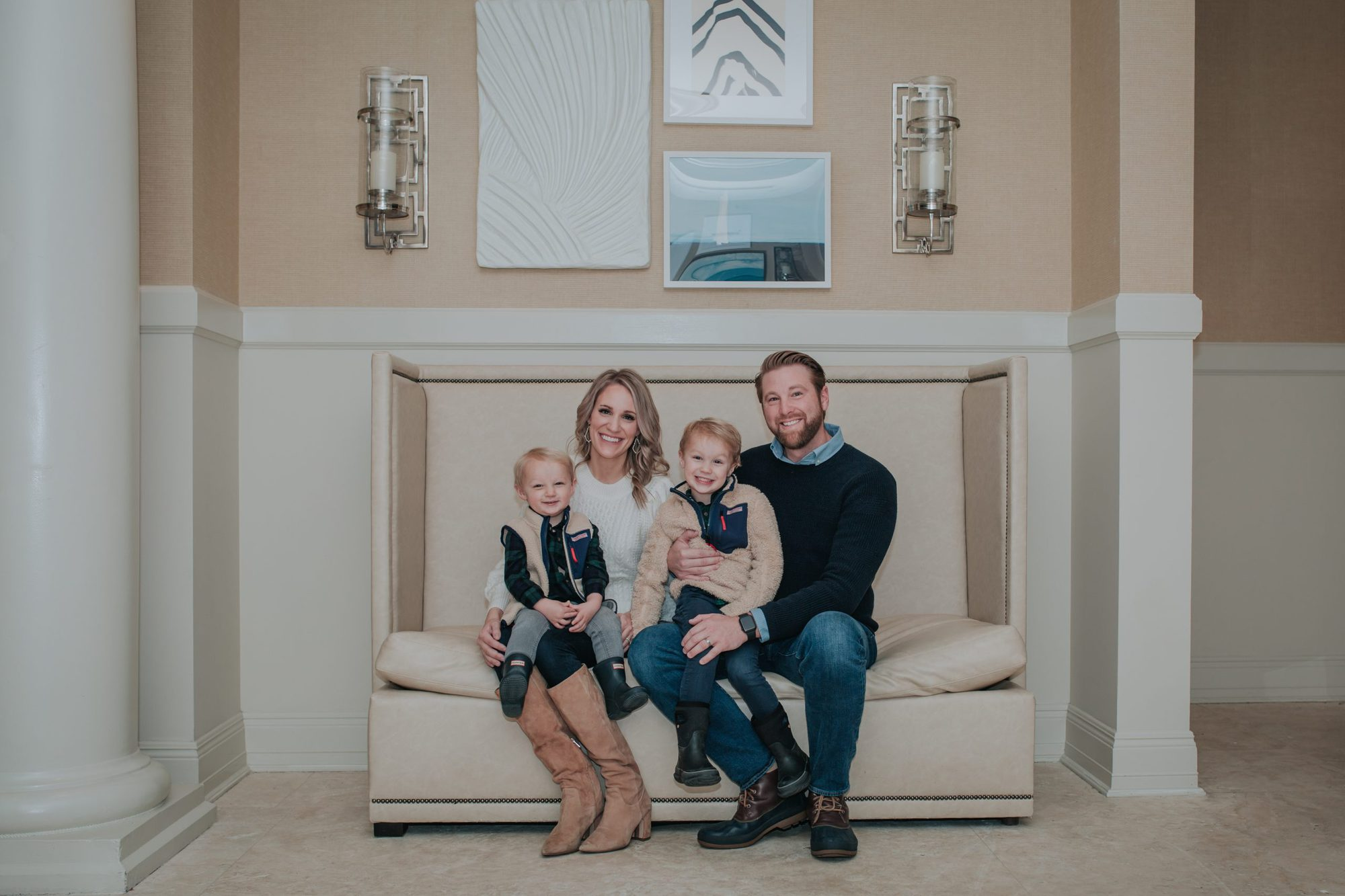 family photo at Inn at Bay Harbor |Inn at Bay Harbor by popular Michigan travel blog, The House of Navy: image of a family sitting together on a couch at the Inn at Bay Harbor.