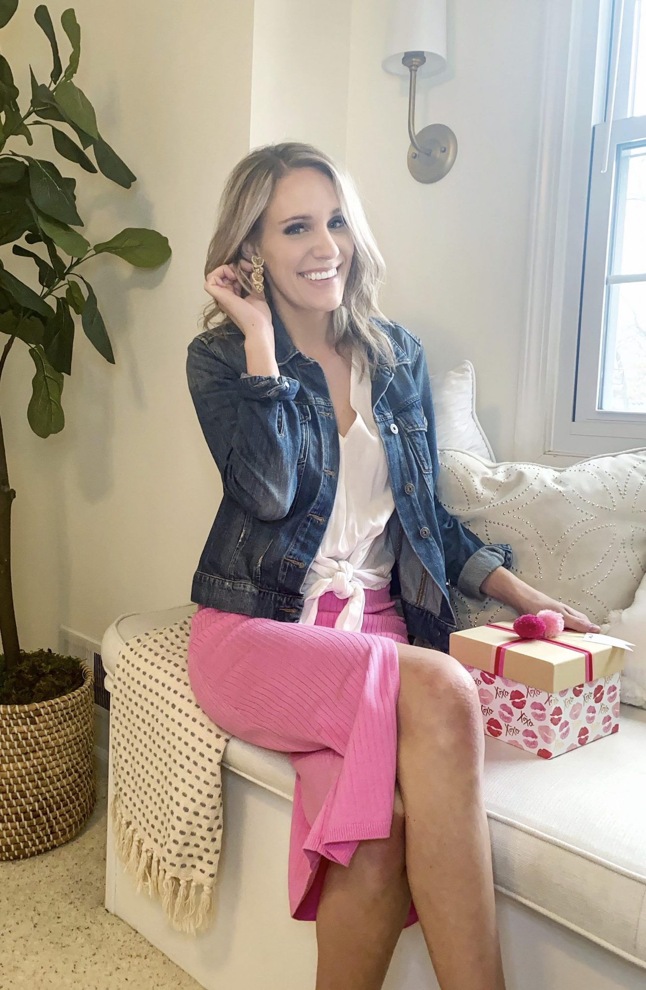 fashionable woman in valentine's outfit |Valentine's Day Gifts by popular Michigan life and style blog, The House of Navy: image of a woman sitting on a white window bench cushion and wearing a white tie waist shirt, denim jacket, pink skirt, and Lily Lough heart drop earrings.