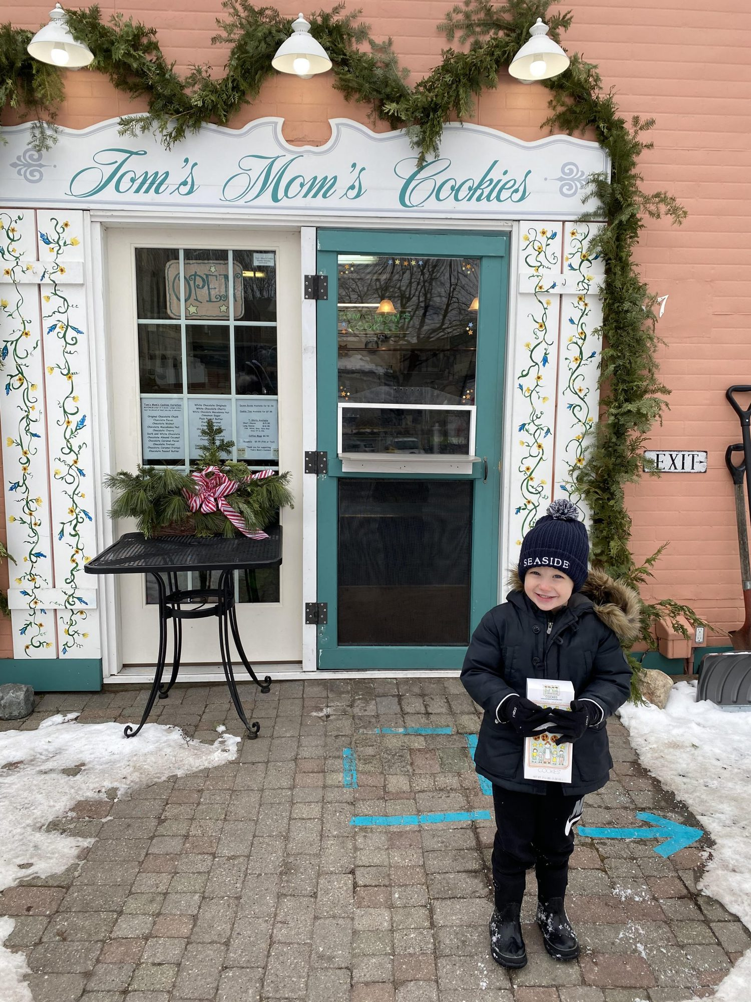 little boy holding box of cookies outside in winter |Inn at Bay Harbor by popular Michigan travel blog, The House of Navy: image of a little boy standing outside Tom's Mom's Cookies.