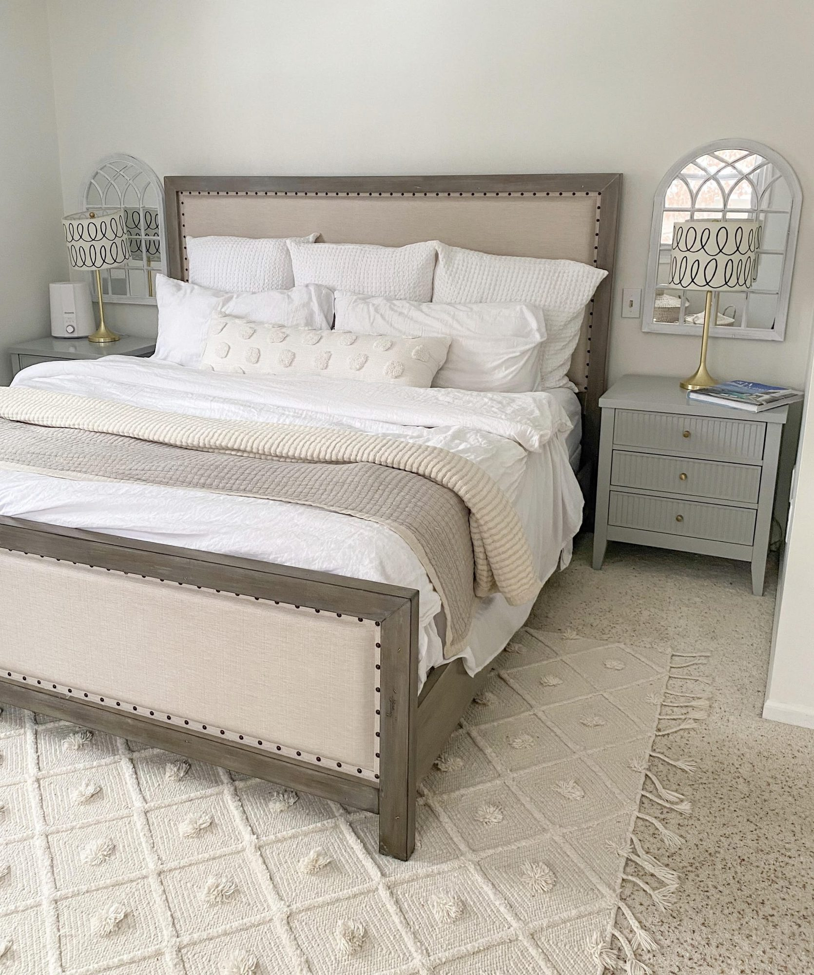 photo of neutral bedroom furniture | Bedside Tables by popular Michigan life and style blog, The House of Navy: image of a master bedroom with cream rug, grey bedside tables, gold lamp stands with white and black lamp shades, and a king size bed with cream and white bedding.