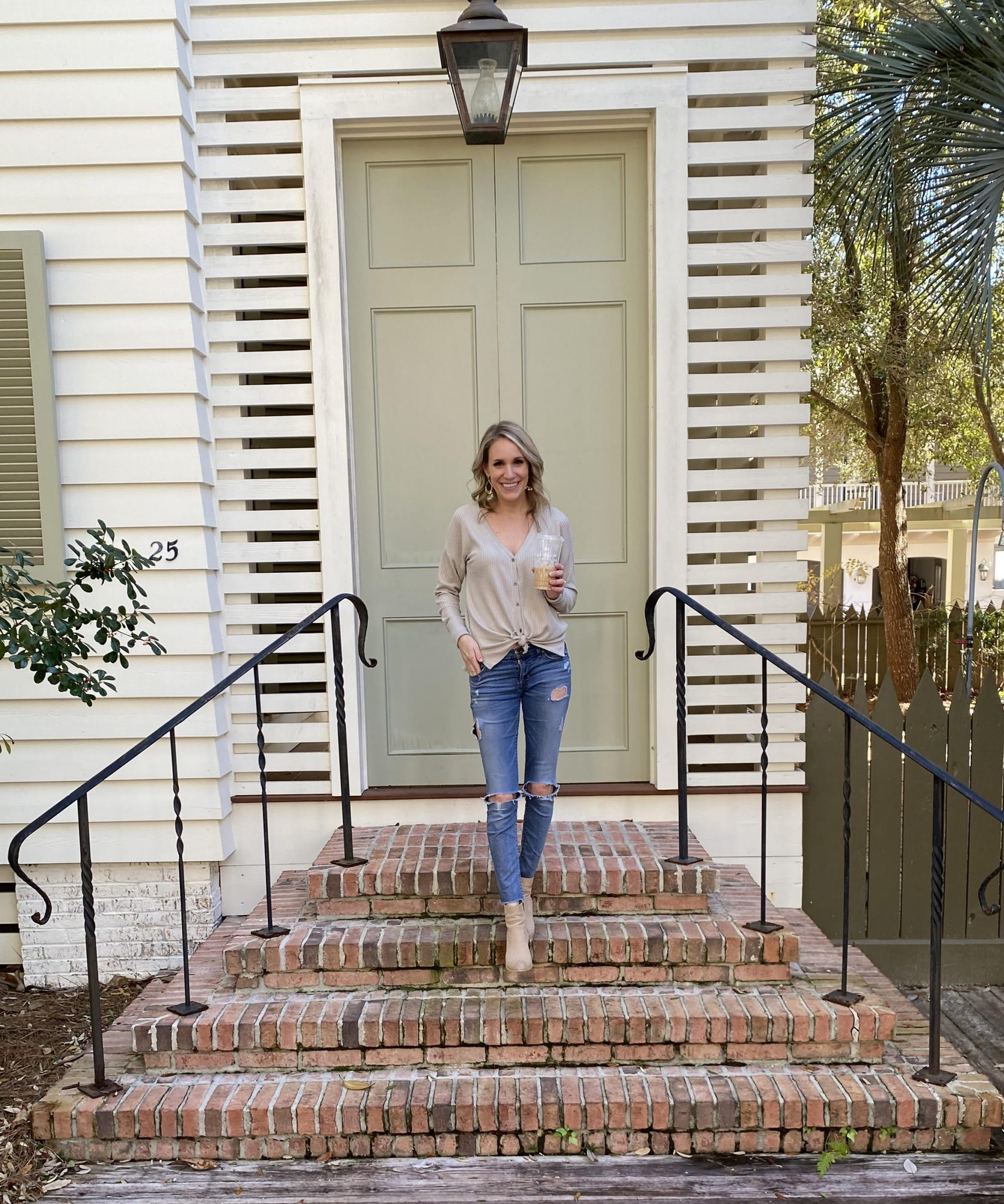fashionable woman walking out of house with coffee |Abercrombie and Fitch Winter Favorites by popular Michigan fashion blog, The House of Navy: image of a woman wearing a long sleeve knot tie shirt, distressed denim, and tan suede ankle boots.