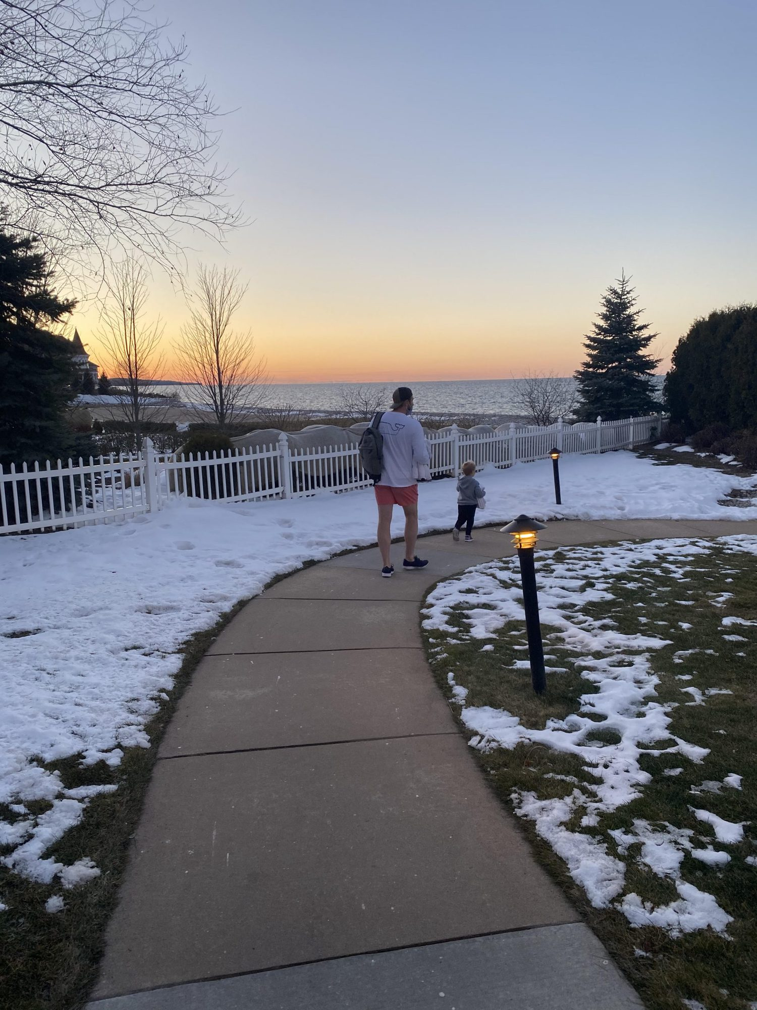 father and son walking outside during winter sunset |Inn at Bay Harbor by popular Michigan travel blog, The House of Navy: image of a dad and his son walking outside on a sidewalk at the Inn at Bay Harbor.