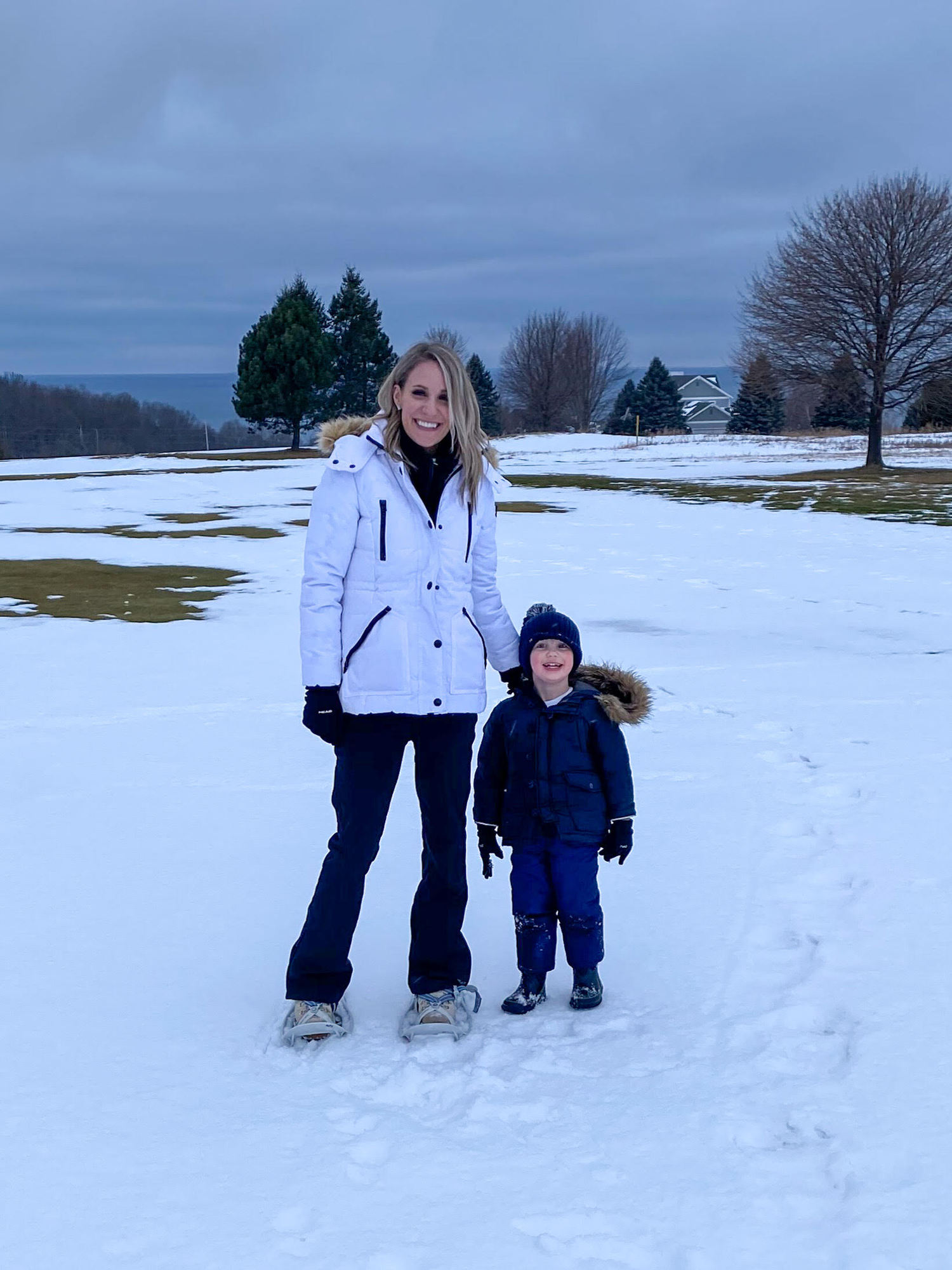 mom and son snowshoeing |Inn at Bay Harbor by popular Michigan travel blog, The House of Navy: image of a mom and her son standing outside in the snow.