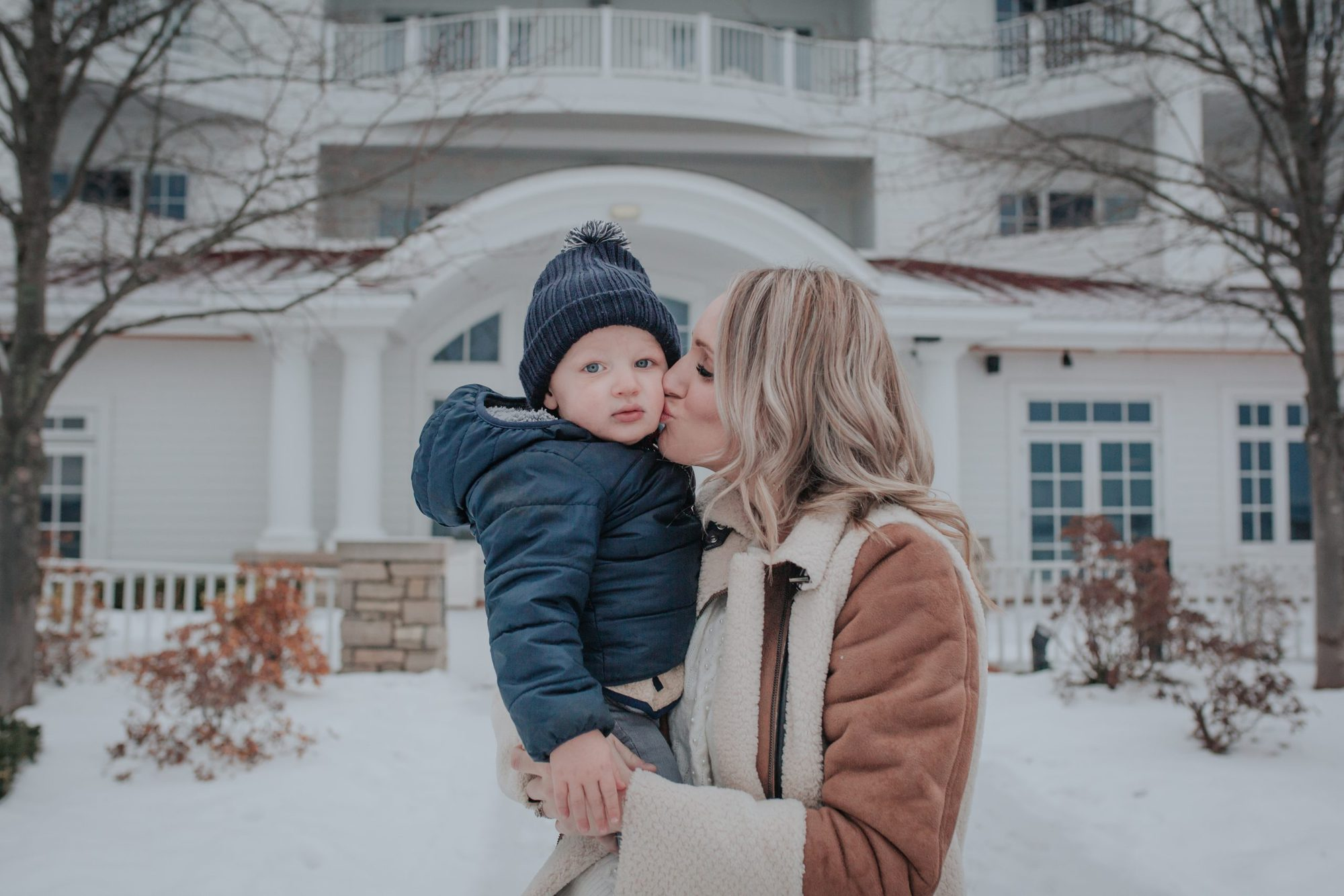 mom holding toddler son and kissing his cheek |Flu Vaccine Benefits by popular Michigan lifestyle blog, The House of Navy: image of a mom holding her young boy outside in the snow and kissing him on the cheek.