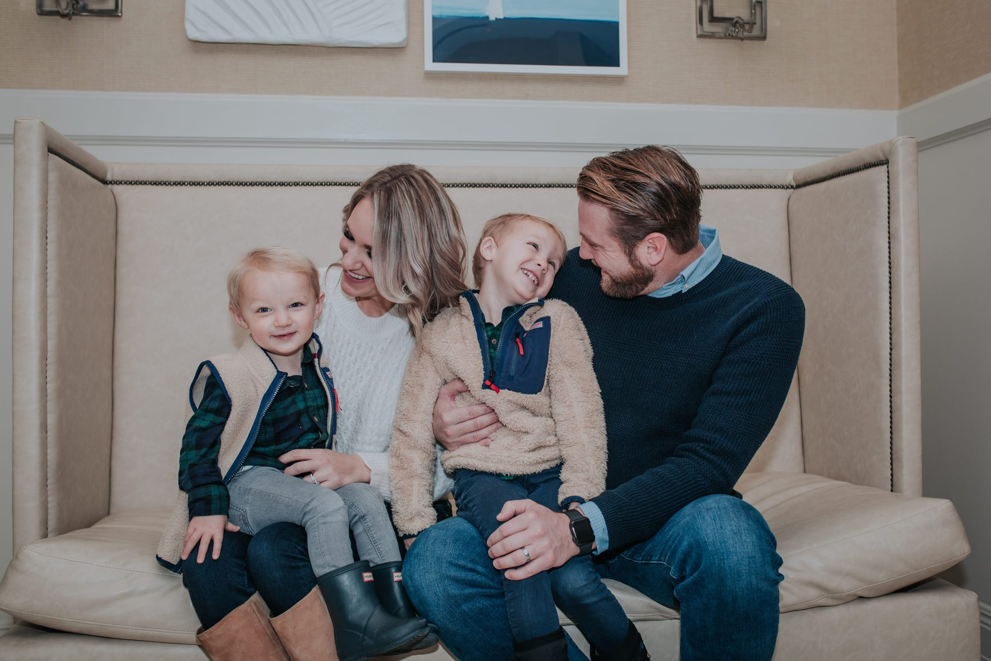 5 Benefits of Getting the Flu Vaccine in Michigan featured by top MI lifestyle blogger, House of Navy: picture of family with two toddler boys laughing | Flu Vaccine Benefits by popular Michigan lifestyle blog, The House of Navy: image of a mom and dad sitting on a tan couch with their two young boys.
