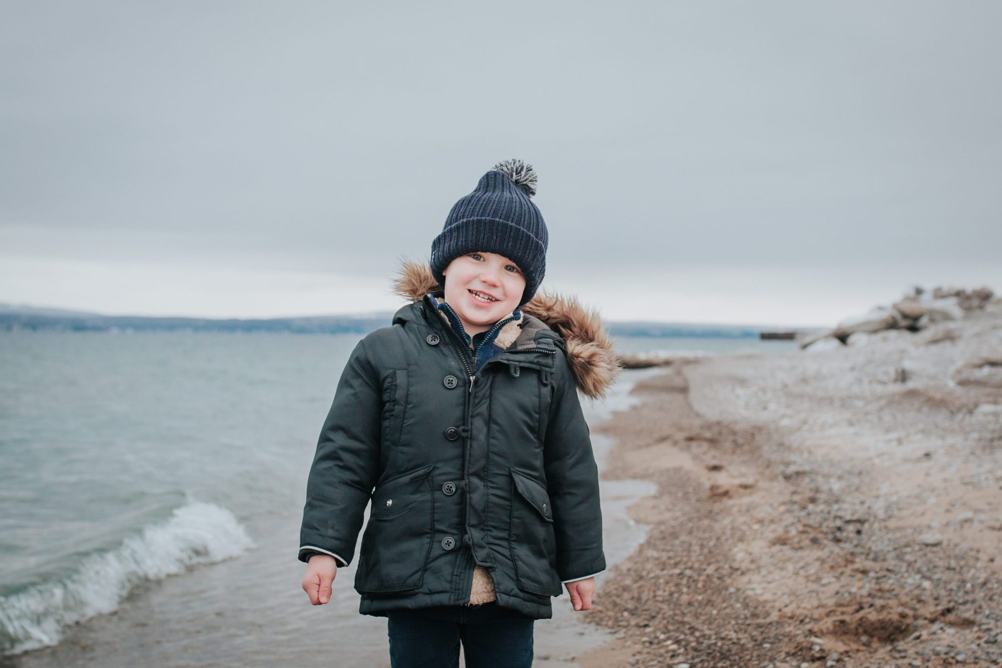 5 Benefits of Getting the Flu Vaccine in Michigan featured by top MI lifestyle blogger, House of Navy: toddler boy smiling near lakeshore in winter |Flu Vaccine Benefits by popular Michigan lifestyle blog, The House of Navy: image of a little boys wearing a fur trimmed hooded coat and blue pom beaning while standing next to the edge of a lake.