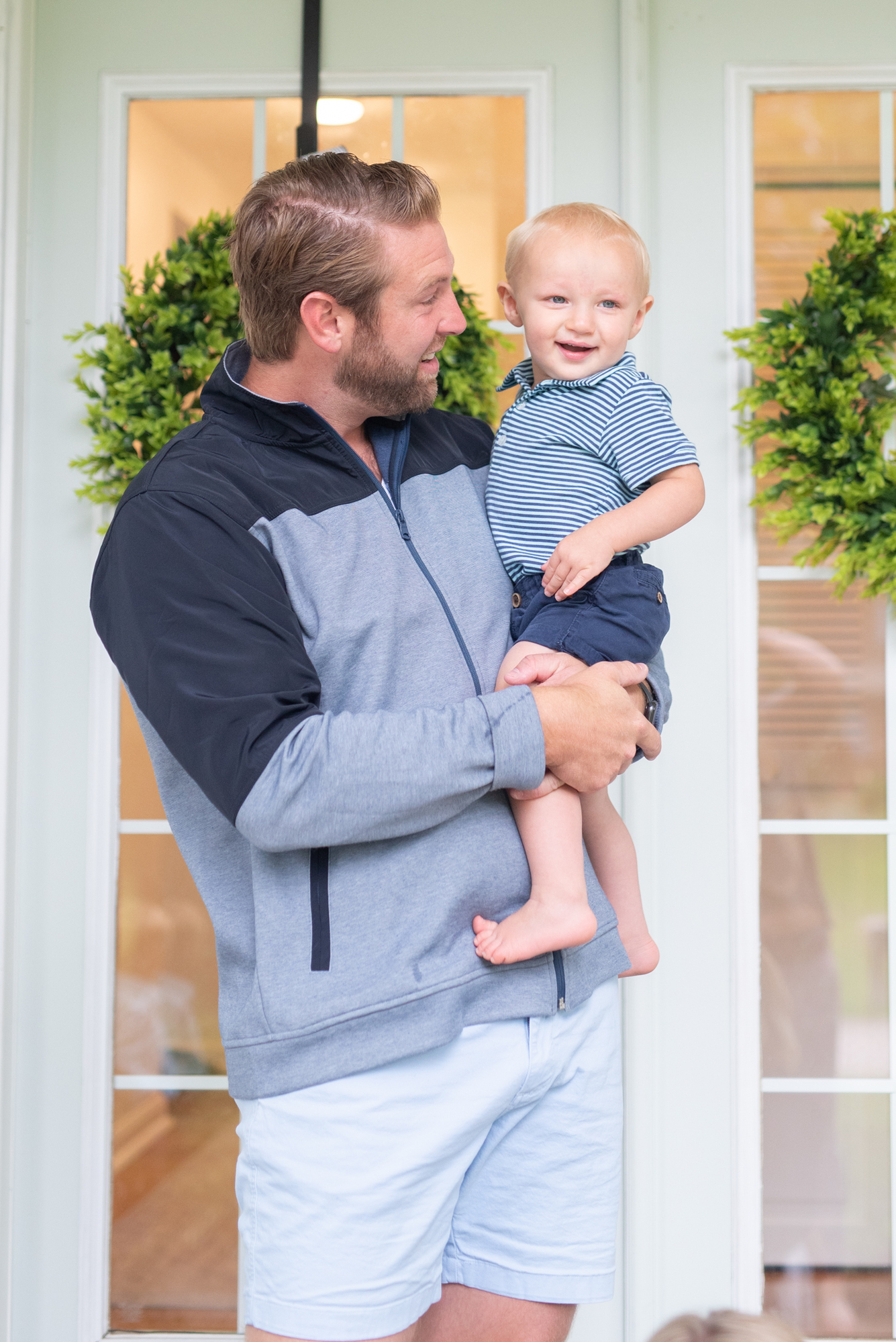 father holding toddler son on front porch